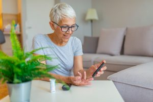 Happy mature woman with glucometer checking blood sugar level at home