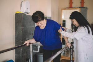 Caring asain chinese female physical therapist helps senior woman stroke victim in rehab center walking with the help of parallel bars